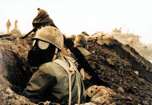 No atheists in this foxhole. An Iranian soldier protects himself against chemicals.