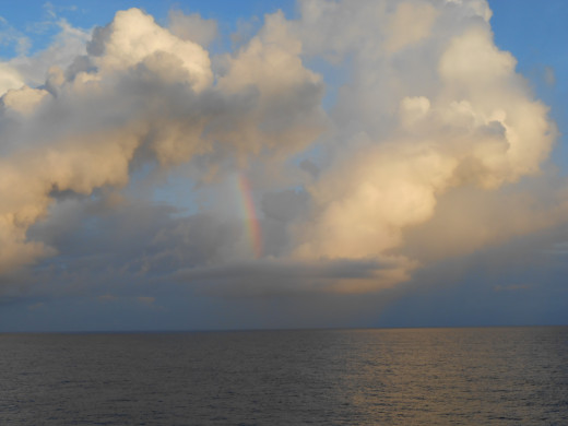 A rainbow in the clouds taken from the balcony of a cruise ship