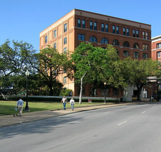 The Texas School Book Depository is along the route of the JFK presidential motorcade.