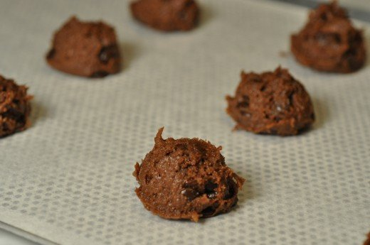 Balls of mixture, dense with chocolate coverture buttons, spaced well apart on baking sheet for baking. Image: © Siu Ling Hui