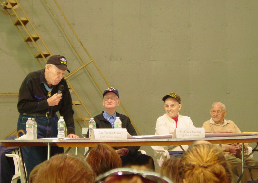 Frank Currey speaks of his exploits at the Battle of the Bulge which won him the Medal of Honor while Owen Mahoney, Robert Cotnoir and Joseph Gosselin look on