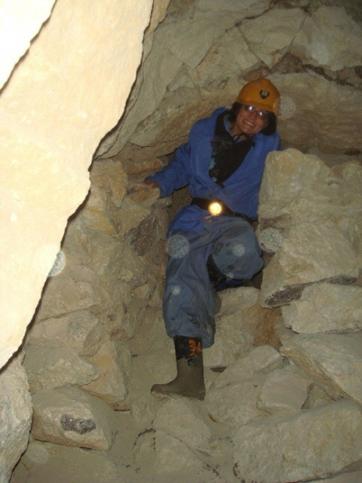 Tourist with safety gear climbing down the narrow holes connecting the underground tunnels.