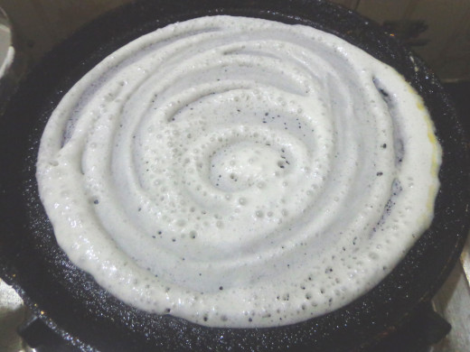 1 ladle of batter is poured  in the center and spread  in a circular motion.