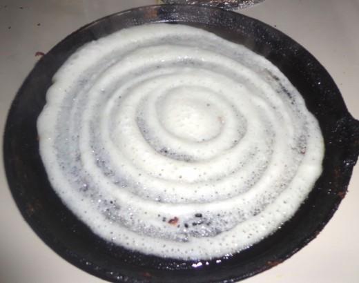 Dosa batter spread in circular motion in tawa