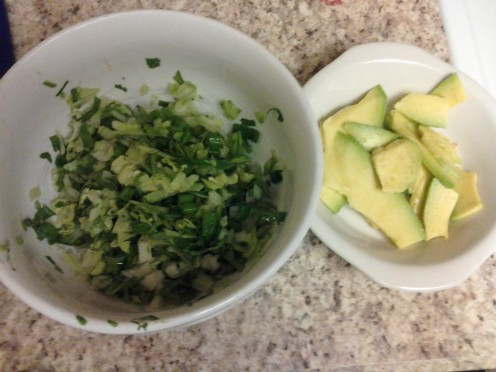 The lettuce mixture and sliced avocado.