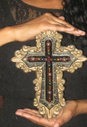 Emunah La-Paz holding the cross represents faith and grace.
