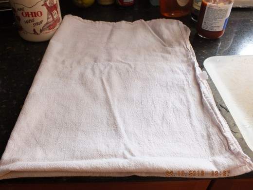 Lay another dry tea towel on top of the tofu.