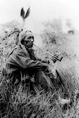 """Chief Good Boy"""" native smoking a long-stemmed pipe"""