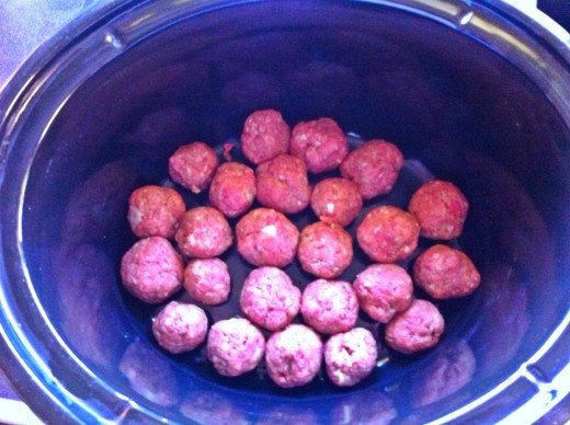Lay meatballs in the base of the slow cooker