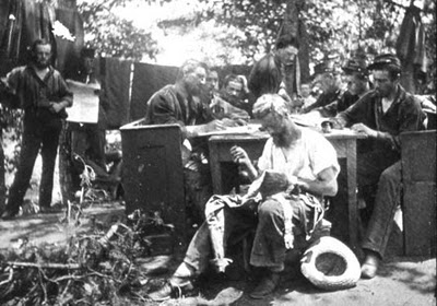 In a posed photograph, while one soldier mends his clothing, others behind him make use of confiscated pews and write letters home. The men in the background pose by laundry or with a newspaper