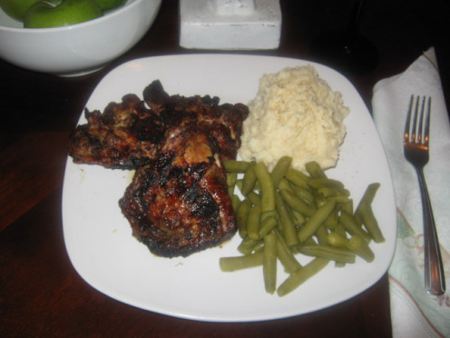 A plate of jerk chicken, Mashed Potatoes, and green beans.