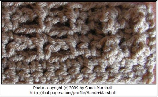 This gives you a closer look at the way the stitches look in the repeat of the pattern. It could be helpful to refer to, as you crochet this dish cloth. This photo shows the right side (the side on which the treble stitches bump out).