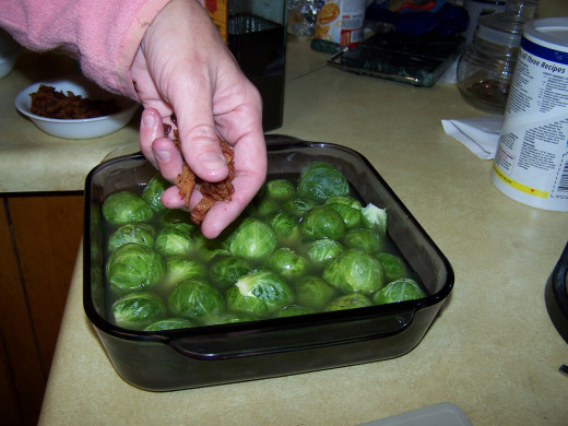 Adding the pre-cooked bacon to the sprouts after the chicken broth has been added.