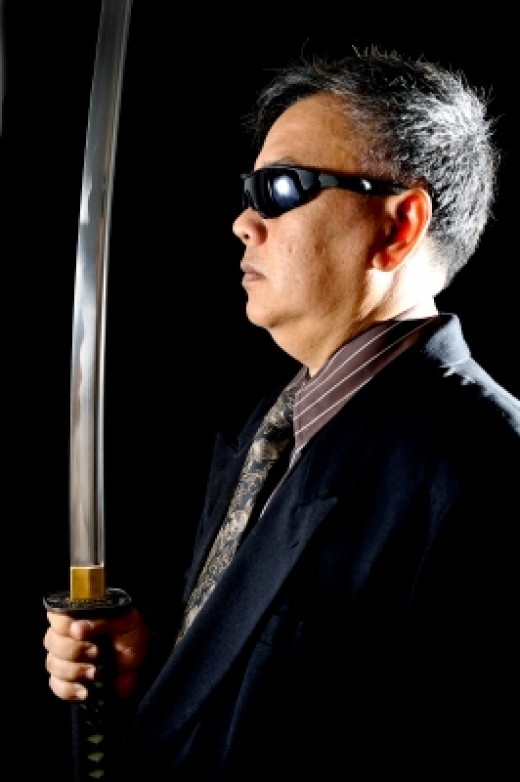 Pictured: probably not a real yakuza. Remember, guns are illegal in Japan... and so are swords.