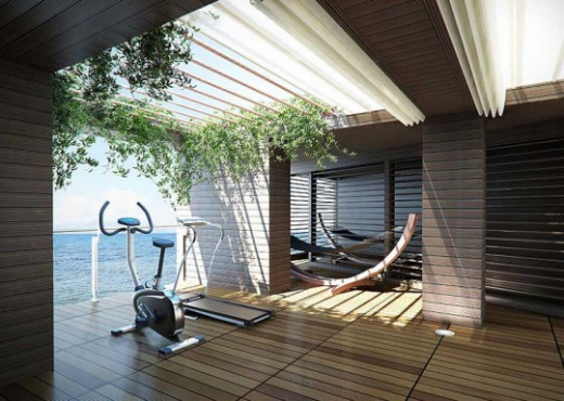 Beautiful view from a home gym - overlooking the water with an exterior patio done artistically in wood for the floors, walls and a sun lite ceiling