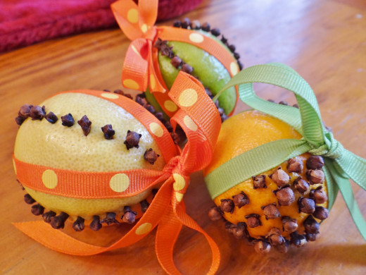 Pomanders are made by inserting cloves in a citrus fruit, wrapping with ribbon and are used as a scented decoration