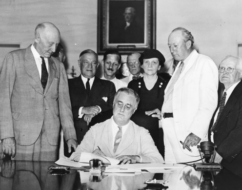 President Roosevelt signs Social Security Act, at approximately 3:30 pm EST on 14 August 1935. Standing with Roosevelt are Rep. Robert Doughton (D-NC); unknown person in shadow; Sen. Robert Wagner (D-NY); Rep. John Dingell (D-MI); Rep. Joshua Twing
