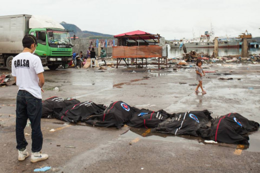 Bodies of Typhoon Haiyan's victims still lie uncollected two weeks after the storm. A Balsa volunteer with mask on prays for the unknown victims.