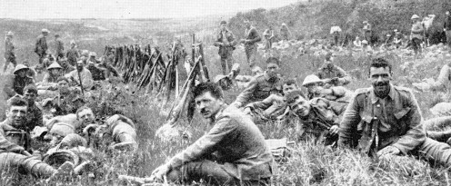 Men of the Royal Irish resting in the long grass behind a rampart In France. Rifles are piled, and the mental tension of war is relaxed. But even through the broad smiles of these loyal men from Ireland one can detect the determination to win.