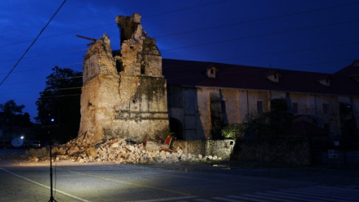 The suppot pillar with Padre Pio's image is still whole. It stands to the right of a small arch entryway and the destroyed bell tower.