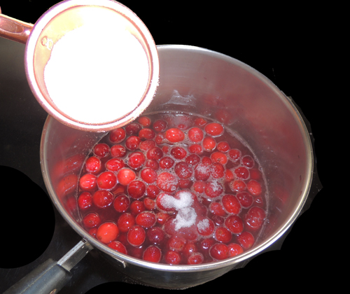 add sugar to simmering cranberries