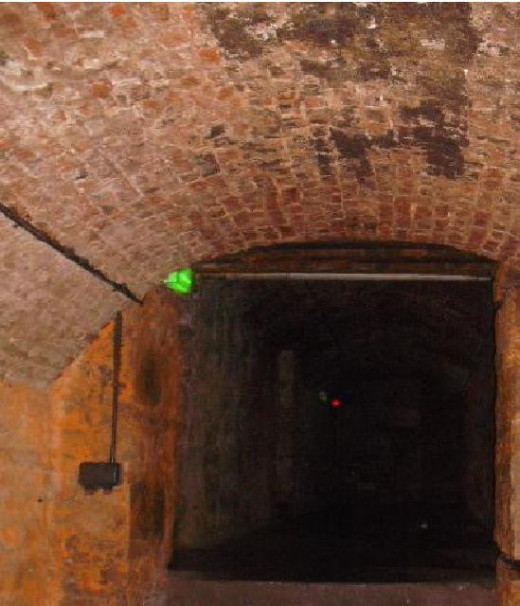 This is a zoomed in picture taken in Edinburgh's South Bridge Vaults. Can you see what looks like a women and child in the middle of the picture?