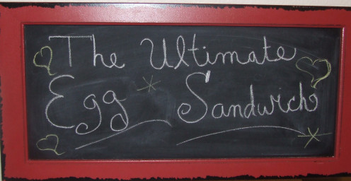 A Chalk Board With Breakfast Ultimate Egg sandwich written down.
