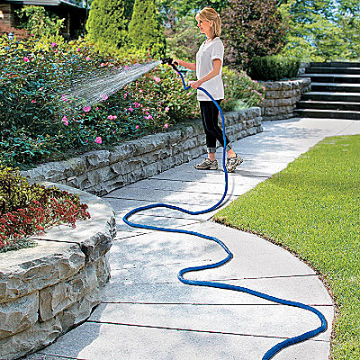 women watering garden with blue XHose fully expanded