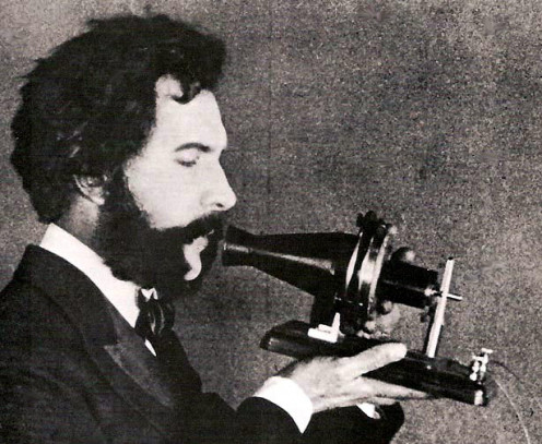 An actor portraying Alexander Graham Bell speaking into an early model telephone.