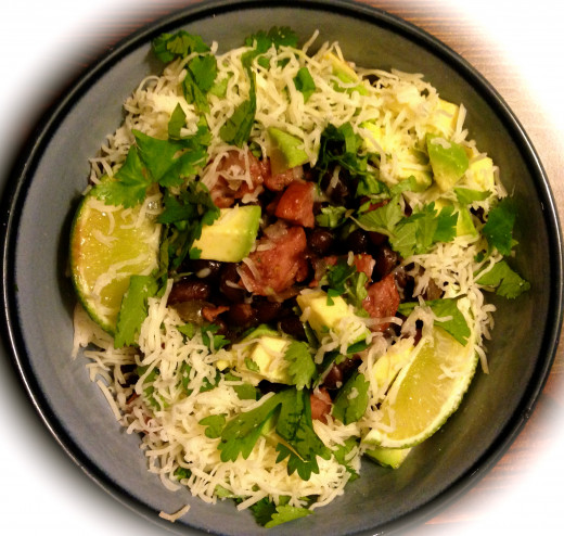 black beans and rice with sausage, topped with cheese, garnished with avocado, cilantro and lime