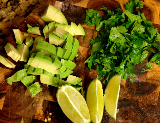 chopped garnishes for beans and rice - avocado, lime, and cilantro