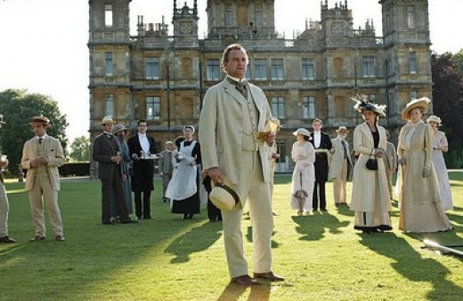 The cast and characters of Downton Abbey.  Highclere Castle of Hampshire pictured in the background is used to depict the fictional estate of Downton.