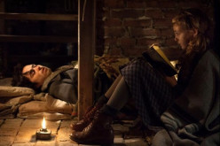 Liesel reads to Max in the basement.