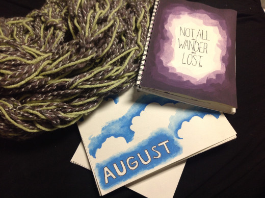 An arm-knitted infinity scarf, a hand painted sketchbook, and a hand painted calendar page.