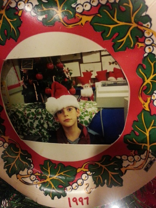 Christmas paper plate ornament with my son's photo on it.  He was wearing a Santa hat and loved making goofy faces then.
