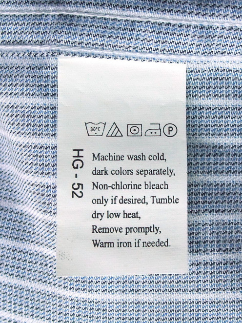 Laundry symbols on a care label attached to a shirt.