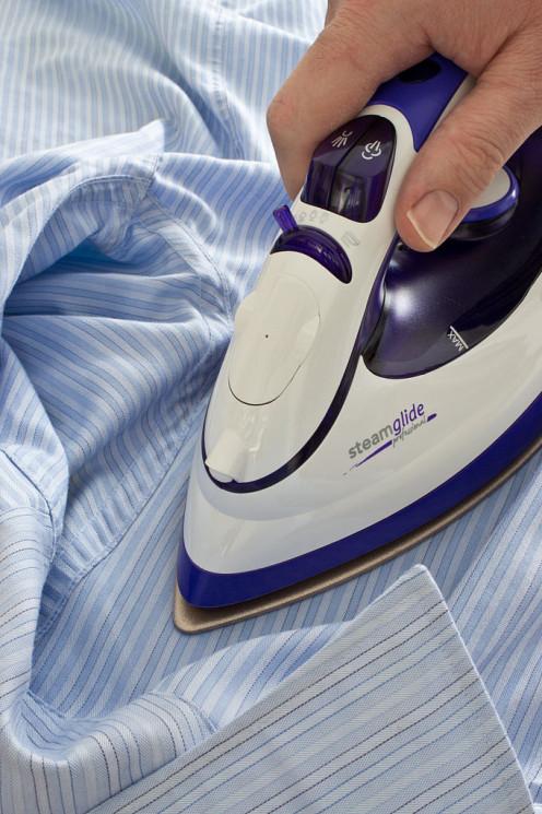 Ironing a shirt using a modern electric steam iron.