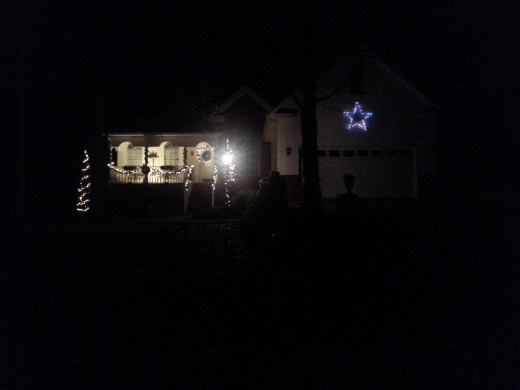 My home at night with the blue star visible over the garage area.