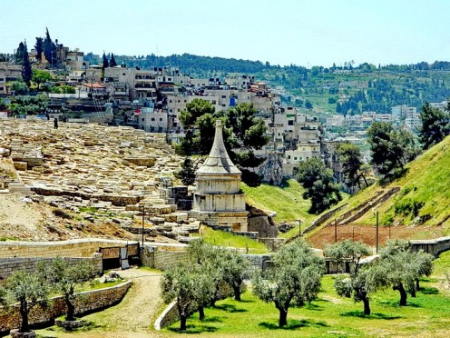 Valley of Kidron. On the left is the Jews cemetery and grave of Absalom is like a conical pillar in the center. Area where Olive trees are standing on green grass used to be deeper and water flowing. The ascend on the right reaches to Jerusalem wall.