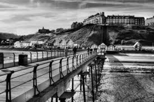 Saltburn pier in its heyday, long, mean and lean - 1950s/1960s view from the outward end back to town