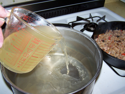 Add chicken broth and begin heating it to a boil.