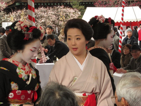 A mature geisha and two maiko, serving tea at the Plum Blossom Festival at Kitano Tenman-gū