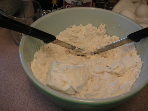 Continue cutting the shortening into the flour using a criss cross motion with two knives.