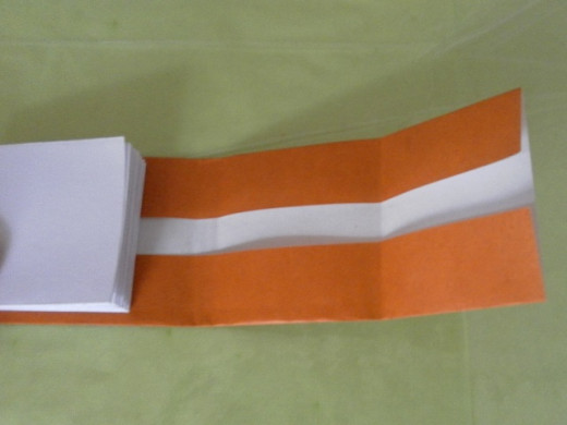 Turn the origami paper over and fold the top and bottom flaps towards the centre. Use the folded pages as a guide to make the right size for the cover. The height of the book cover should be a one or two mm taller than the height of the pages