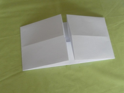 Bring the left and right flaps of the paper to the centre so that their edges align with the centre crease line.