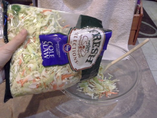 Step One: Pour your pre-made coleslaw mix into a large bowl (larger than the one you see, I had to switch to something bigger)