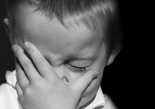 Image of little boy covering his face.