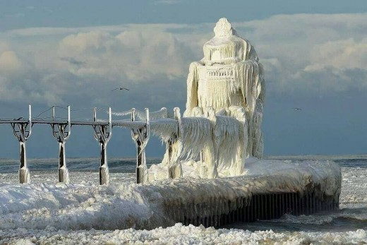 Display of solid ice chunks and dramatic Icicles on light head of North Pier in St. Joe, Michigan near Silver Beach