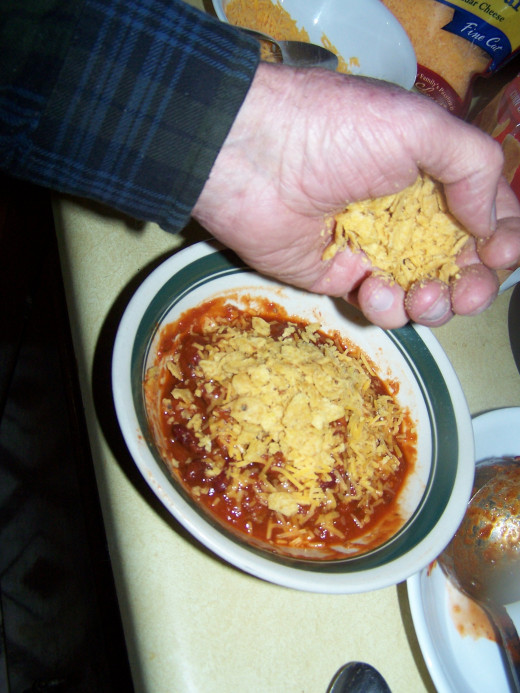 Me adding my Fritos to the chili that I made.