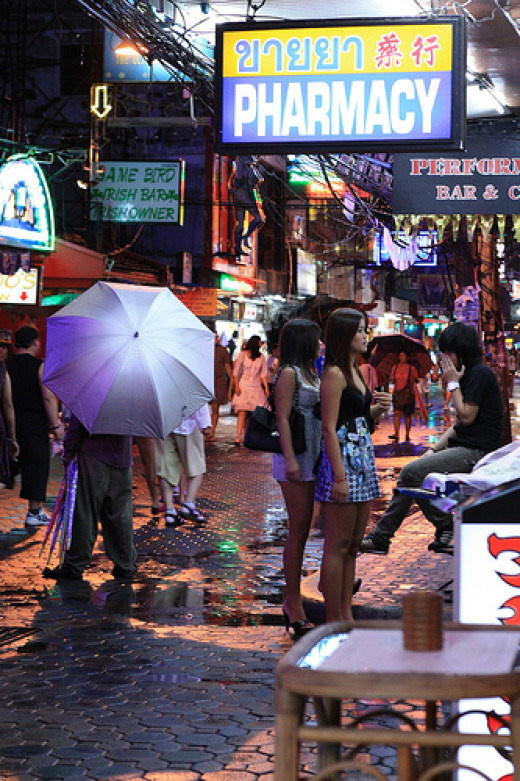 Two girls and an umbrella on Walking Street in Pattaya from faragrakthai.com flickr.com